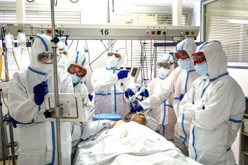 أطباء وممرضون يعالجون مريضاً بكوفيد-19 في العناية المكثفة بمستشفى قرب مدريد.