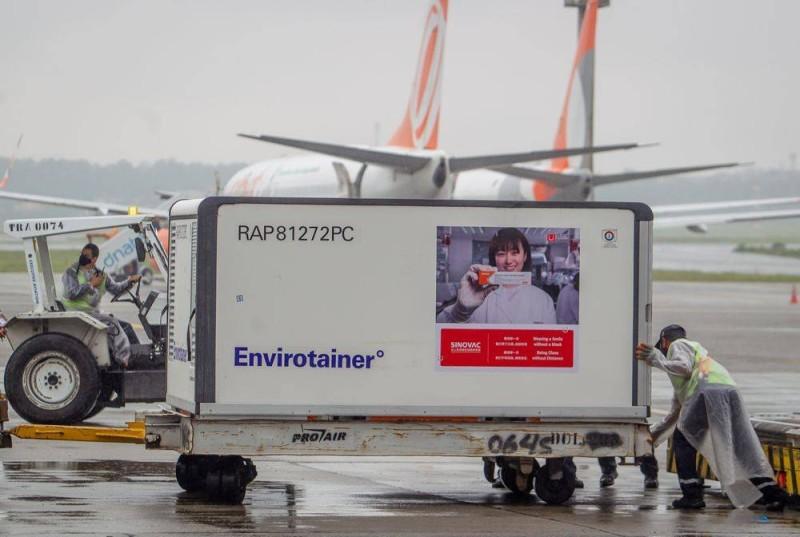 عمال مطار ساو باولو البرازيلي يقومون بإنزال حاوية مبرَّدة تحمل لقاح ساينوفاك الصيني من طائرة صينية.