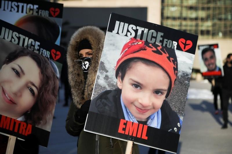 أهالي الضحايا يرفعون صورهم خلال وقفة احتجاجية في تورونتو أمس.