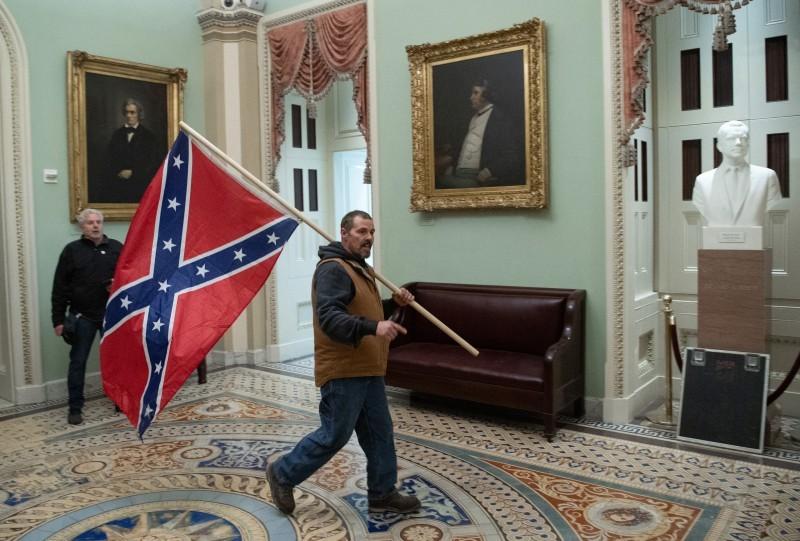 متظاهر في مبنى الكونغرس يحمل العلم الفيدرالي.