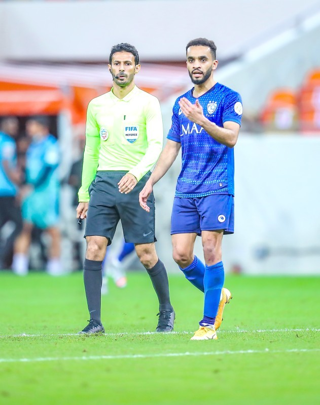الحكم ماجد الشمراني ولاعب الهلال محمد البريك أثناء مباراة الكلاسيكو. (تصوير: متيم العصيمي)