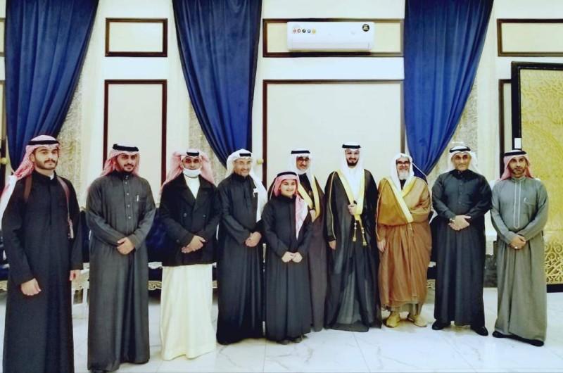 العريس يتوسط والده وأقاربهما.