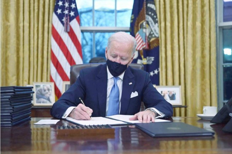 بايدن يوقع أوامره التنفيذية الأولى في المكتب البيضاوي يوم الأربعاء 20 يناير 2021 ، في واشنطن.