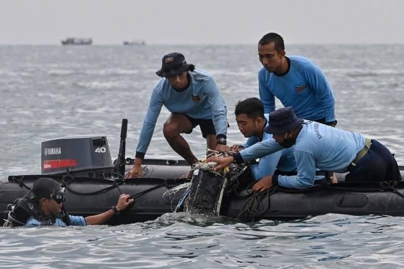 منقذون إندونيسيون خلال إخراجهم أجزاء من حطام الطائرة المنكوبة أخيراً.