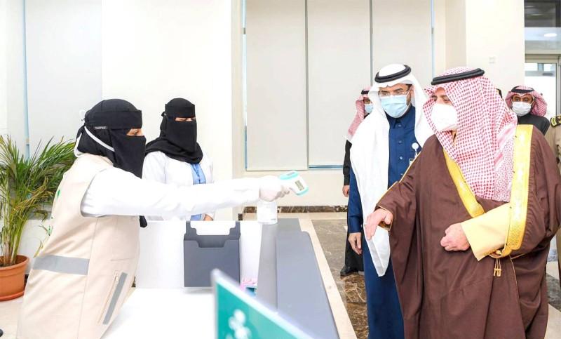 الأمير فهد بن سلطان يخضع لقياس درجة الحرارة قبل انطلاق جولته بمركز اللقاحات.