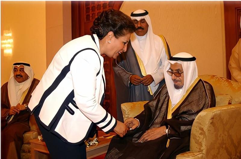 سعاد الحميضي تصافح أمير الكويت السابق الشيخ جابر الأحمد في إحدى المناسبات.