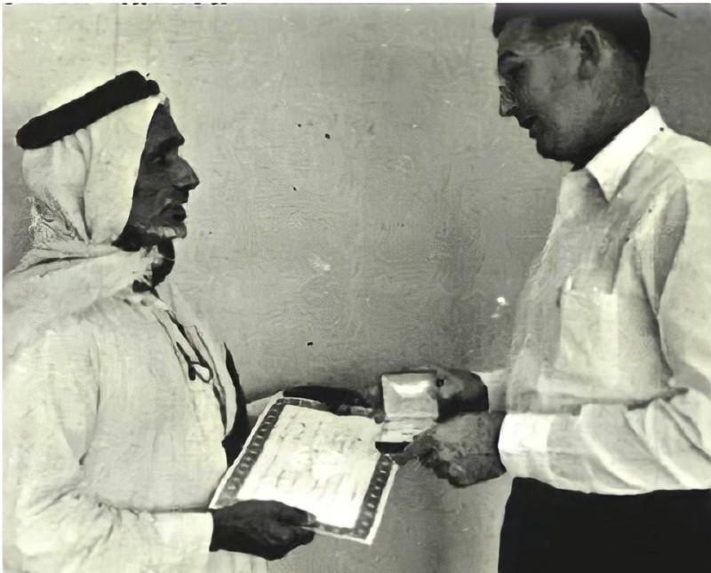 بن رمثان يتسلم من نائب رئيس أرامكو بارقر شهادة إتمام 15 عاماً من العمل مع أرامكو في ديسمبر 1957.