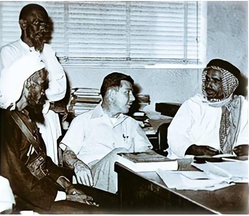 الدكتور جورج رينتز من شركة أرامكو يتحدث إلى بن رمثان وبعض قصاصي الأثر بمكتبه في الظهران عام 1950.
