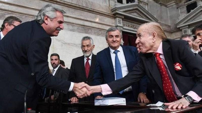 كارلوس منعم مصافحاً الرئيس الأرجنتيني ألبرتو فيرنانديز