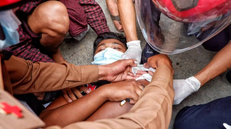 مصاب يتلقى العلاج إثر سقوطه في المواجهات بين المحتجين وقوات الانقلاب في ميانمار أمس.