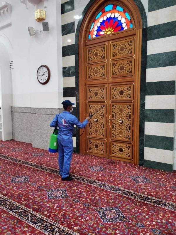 عامل نظافة يعقم جوانب باب أحد المساجد.