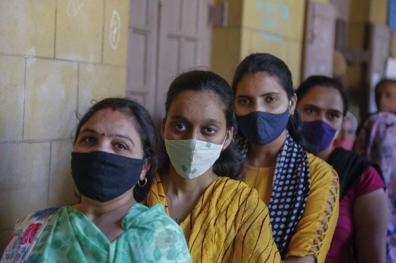 هنديات يدلين بأصواتهن في الانتخابات بأحمد أباد ويعتمدن على الكمامة لحمايتهن من الفايروس.