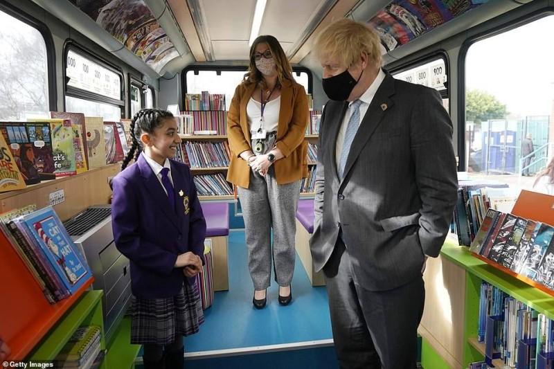 جونسون مع تلميذة على متن حافلة الكتب بمدرسة سانت ماري في لندن.