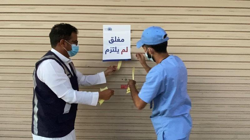 مراقب بلدية يغلق محلاً مخالفاً. (تصوير: مديني عسيري)