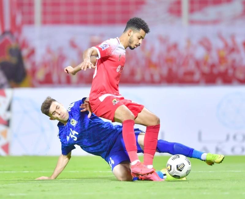 مدافع الوحدة نور الرشيدي يبعد كرة من أمام لاعب القوة العراقي.