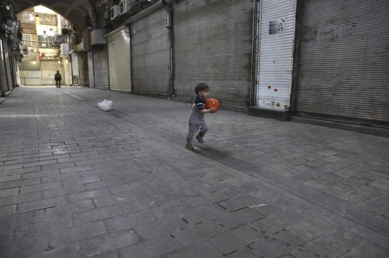 طفل يلعب أمام المتاجر المغلقة في بازار طهران الكبير.