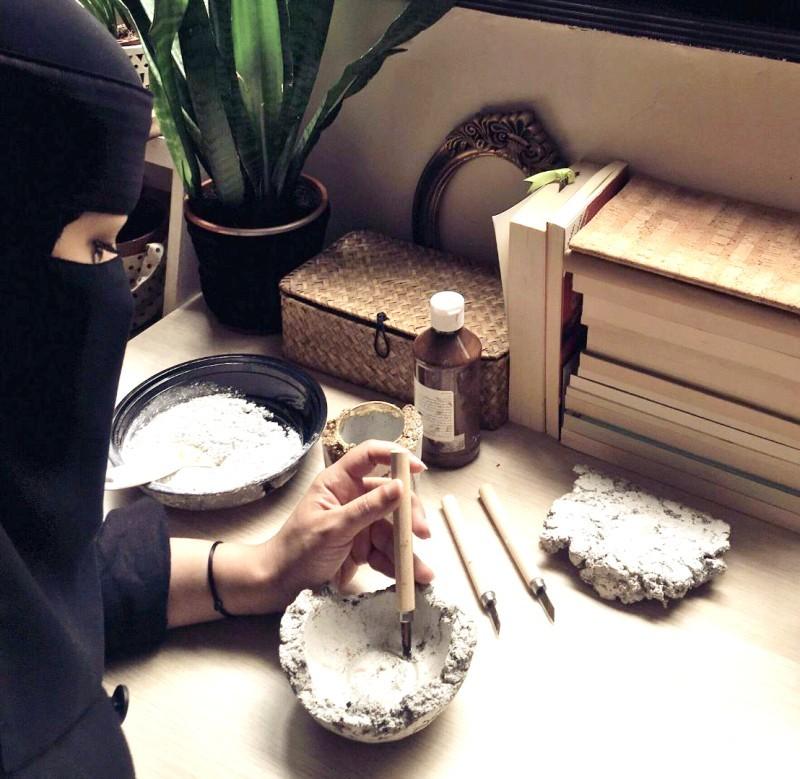 رشا الجهني أثناء صنع قطعة تراثية.