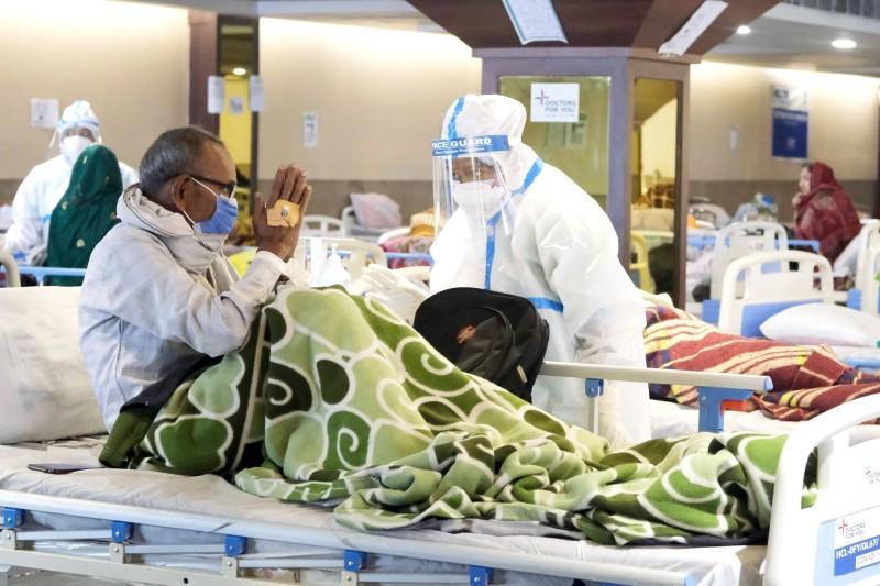 كادر صحي يساعد مصاباً بالفايروس في مستشفى ميداني في نيودلهي.