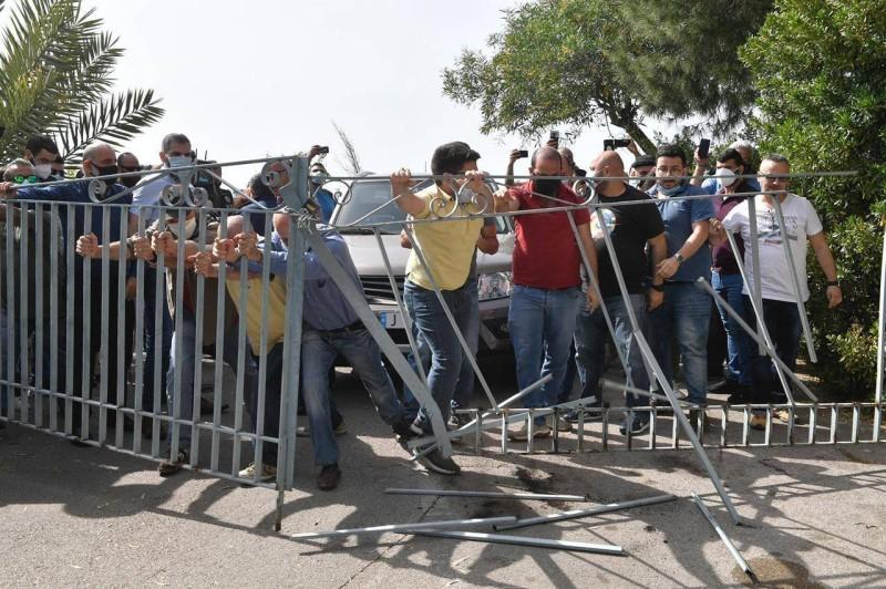 مناصرو التيار العوني يخلعون البوابة لدخول سيارة القاضية عون إلى باحة الشركة.