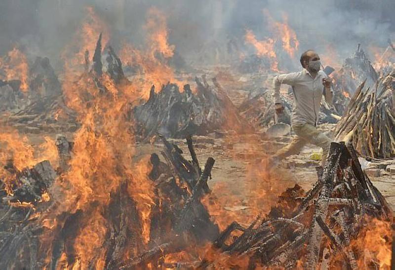 هندي يركض للنجاة من حرارة نيران محرقة الجثامين التي لا تخمد في نيودلهي.