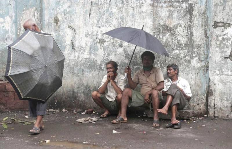 عمال بالأجر اليومي ينتظرون أرزاقهم في أحد شوارع مموباي. (وكالات)