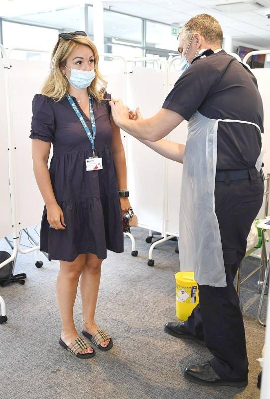 ممرض يقوم بتطعيم امرأة في مقاطعة شيشاير البريطانية. (وكالات)
