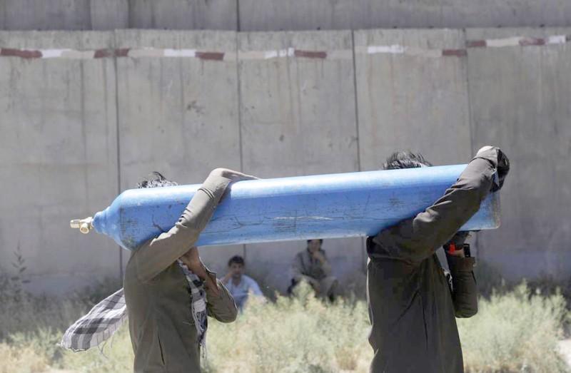 شخصان يحملان أسطوانة أكسجين طبي فارغة في كابول.