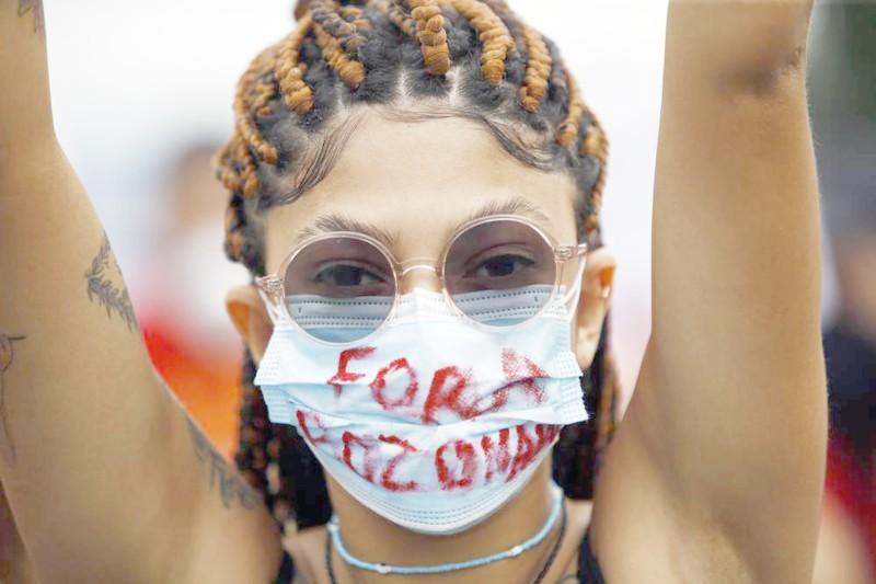 متظاهرة برازيلية ارتدت كمامة عليها مطالبة بمساءلة بولسونارو. (وكالات)
