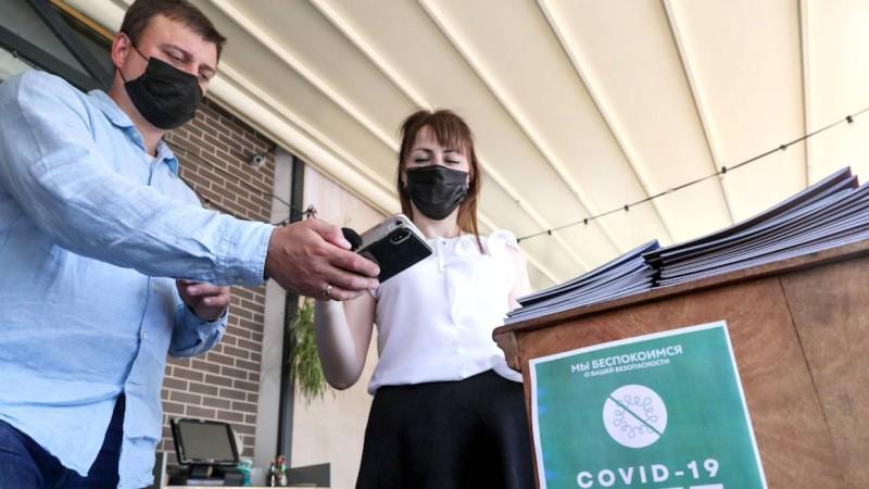 نادلة تتأكد من شهادة تطعيم زبون أحد مطاعم موسكو. (وكالات)