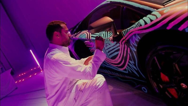 قنديل أثناء انشغاله بالرسم على إحدى السيارات.