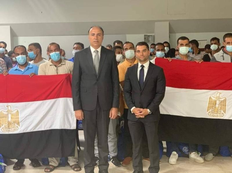 ممثلو السفارة مع المصريين العائدين من ليبيا