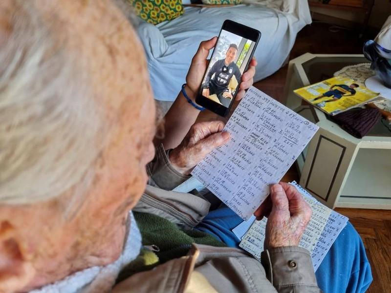 هرنان ماسترانجيلو، صانع الشوكولاتة السابق البالغ من العمر 100 عام ومن محبي نجم كرة القدم الأرجنتيني ليونيل ميسي، يحمل ملاحظاته المكتوبة بخط اليد عن أهداف ميسي، ويشاهد مقطع فيديو أرسله له ميسي عبر جوال حفيده جوليان، في بوينس آيرس، الأرجنتين. (رويترز)
