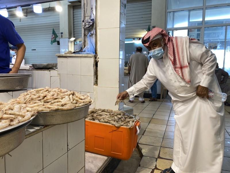 مواطن يتفحص الروبيان قبل شرائه في سوق الدمام المركزي للأسماك أمس. (تصوير: محمد الشهراني)