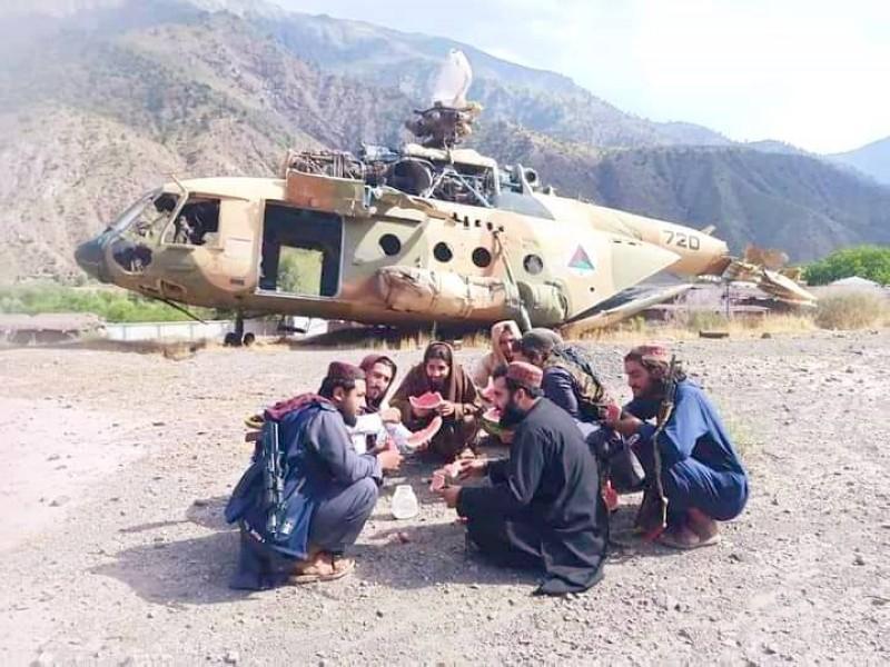 مقاتلون من طالبان أمام إحدى المروحيات المدمرة التابعة للجيش الأفغاني، وفي الإطار جندي أفغاني يحرس إحدى المناطق. (متداولة)