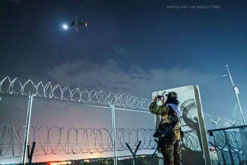 مقاتل من طالبان يصور آخر طائرة أمريكية غادرت كابول. وفي الإطار القائد الأمريكي يتأهب لركوب الطائرة.  (متداولة)