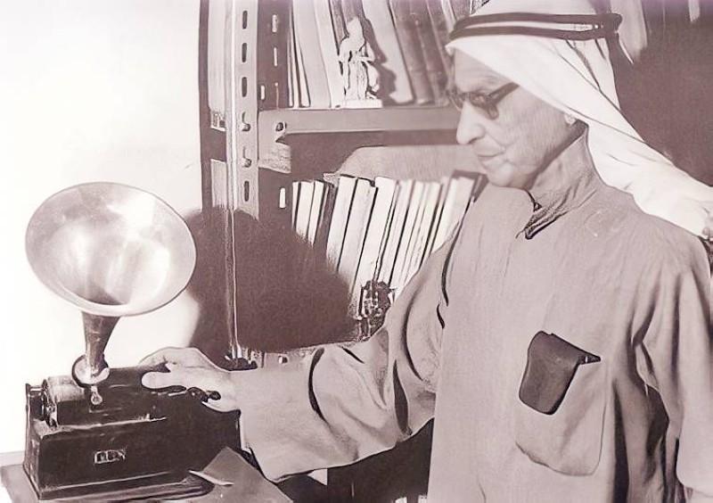 .. ويعاين جهاز الغرامفون القديم سنة 1981 داخل مكتبته العامرة.