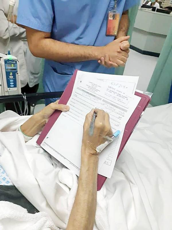 الدميني يوقّع بالموافقة على العملية الجراحية.