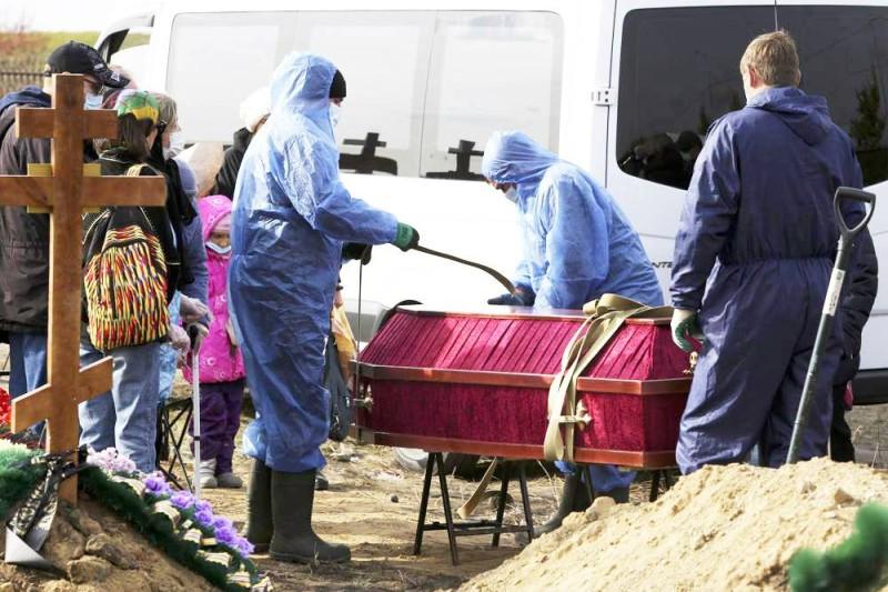 عمال مقبرة قرب موسكو يقومون بتعقيم جثة متوفى بكوفيد تمهيداً لمواراتها. (وكالات)