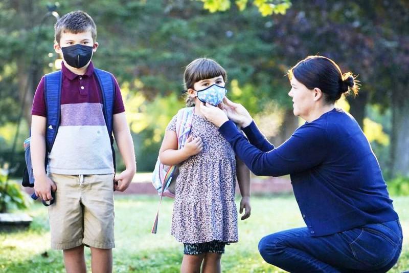 أم أمريكية تقوم بتعديل وضع كمامة طفلتها في الطريق للمدرسة. (وكالات)