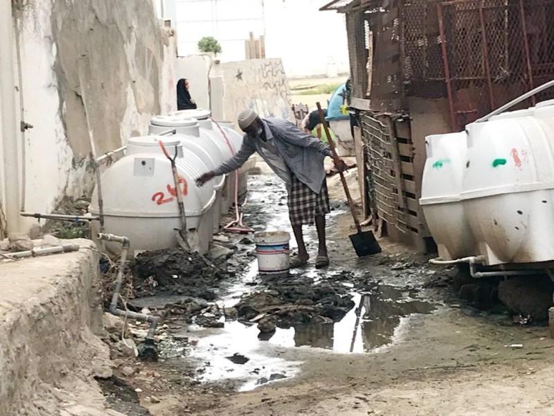أحد السكان يقف أمام خزان ماء نصبه في الشارع لمعالجة نقص المياه.